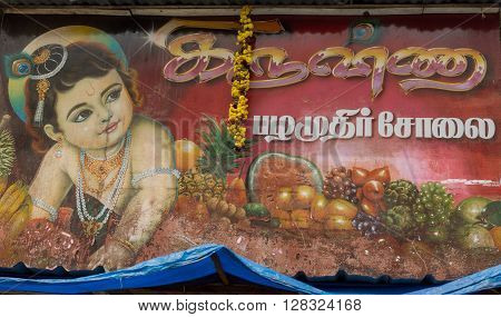 Trichy India - October 15 2013: Billboard on which Lord Krishna promotes the business of a fruit vendor in the streets near Shirangam Temple. Toddler playing among pineapple tomatoes grapes and more.