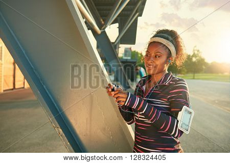 Attractive african american girl listening to music on her smart phone fo an urban jog  at summer sunset