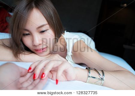 Young Asia woman playing her boyfriend hand on a bed in a bedroom , Concept of couple, romantic and couple concept.