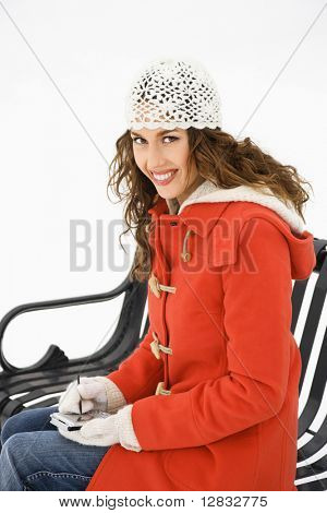 Caucasian young adult female in winter clothing sitting on park bench using PDA and smiling at viewer.