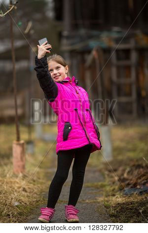 Little girl makes selfie on phone while standing outdoors.