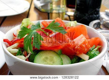 A delicious mixed salad of tomatoes, cucumber, cabbage, onion, paprika and lettuce in white porcelain bowl.