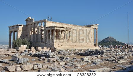 ATHENS, GREECE - OCTOBER 18: Erechtheion ancient greek temple dedicated to both Athena and Poseidon with the famous Porch of Caryatids at the top of the Acropolis of Athens and Mount Lycabettus OCTOBER 18,  2014 in Athens, Greece