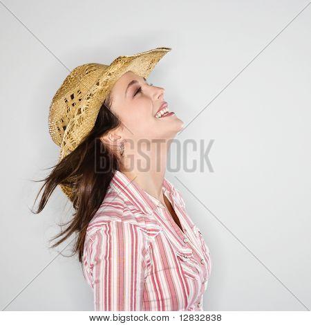 Profil von junge Caucasian Frau Cowboy Hut lächelnd mit Wind weht Haar trägt.