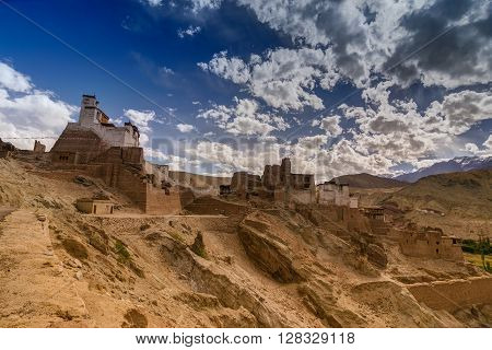 Ruins and Basgo Monastery surrounded with stones and rocks Leh Ladakh with blue sky with clouds in the background India