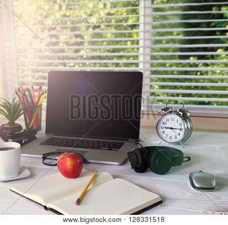 Working desktop in front of large window with bright daylight and trees in background. Light effect applied to image.