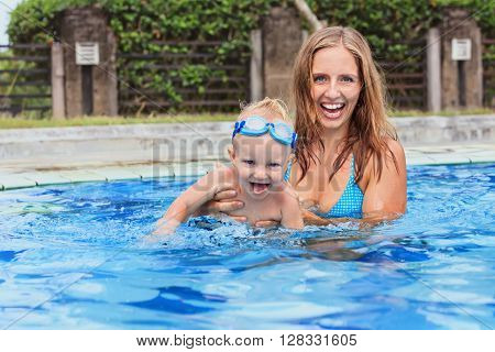 Photo of happy family - swimming and having fun woman and little child in goggles. Focus on baby. Family lifestyle and water sport activity swimming lessons with parents in pool on summer vacation.