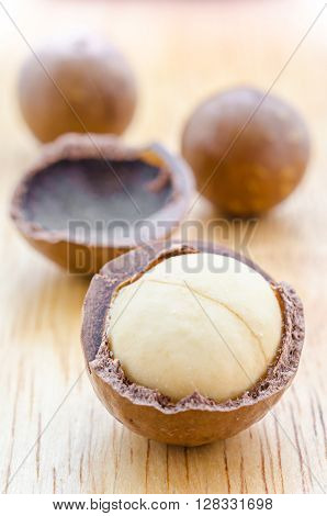 Close up the macadamia nuts on wooden background.