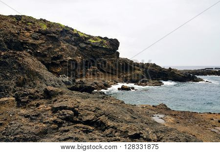 Waves Crash Against The Rugged Volcanic Coastline