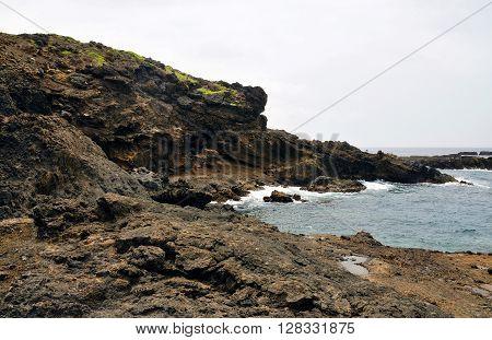Waves Crash Against The Rugged Volcanic Coastline