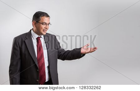 indian Businessman isolated over white background presenting copy space. asian Happy business man giving presentation on copy space, Happy business man giving presentation on white background