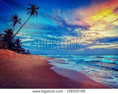 Beach holidays vacation romantic concept background - vintage retro effect filtered hipster style image of sunset on tropical beach with dramatic cloud sky. Sri Lanka