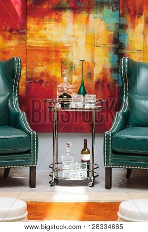 California, United States -- April 29, 2016: Alcohol decanter, bottle of Chambord liqueur, red wine and glasses on a glass serving table between two chic blue green leather chairs in front of a red, orange and yellow abstract painting.
