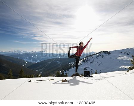 Young woman doing yoga pose on rock in snow in mountainous terrain.