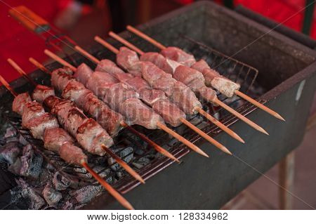 Grilling marinated shashlik on a grill