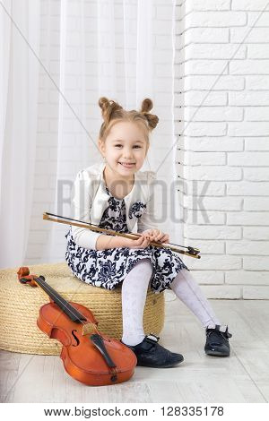 little girl sits holds a bow and showing tongue looking at camera