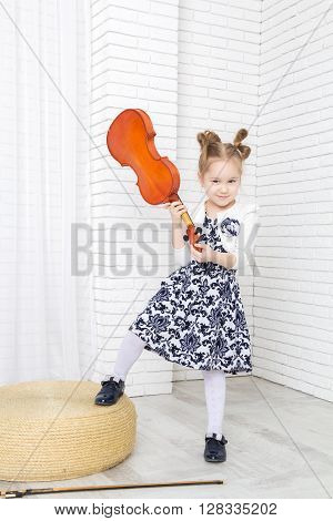 little girl swings violin looking at camera