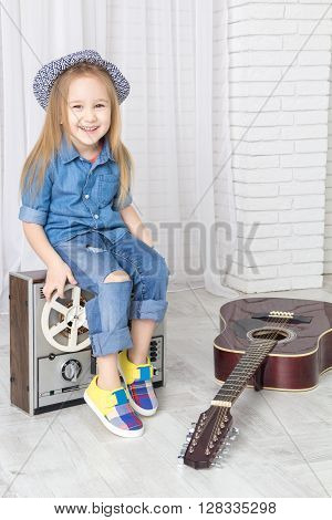little girl sitting on retro tape recorder and laughs looking at camera