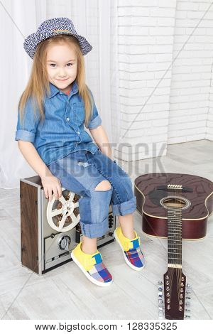 little girl sitting on retro tape recorder and guitar lies near looking at camera