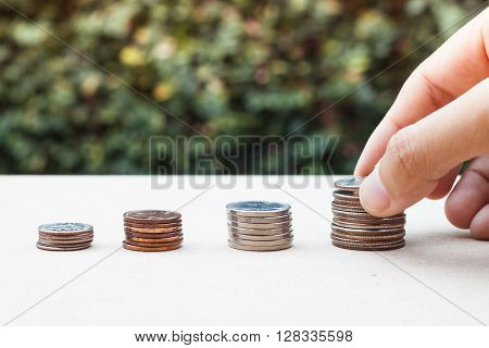 Woman hand putting money coin for saving money concept