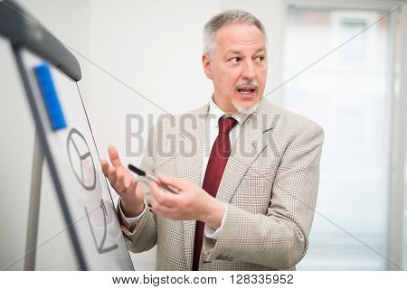 Businessman showing data on a whiteboard during a meeting