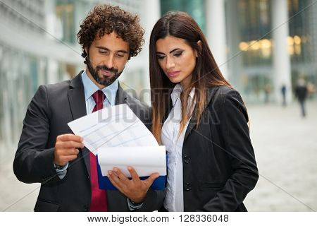 Portrait of business people reading a document