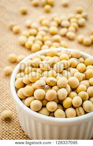 Soy beans in white bowl on sack background.