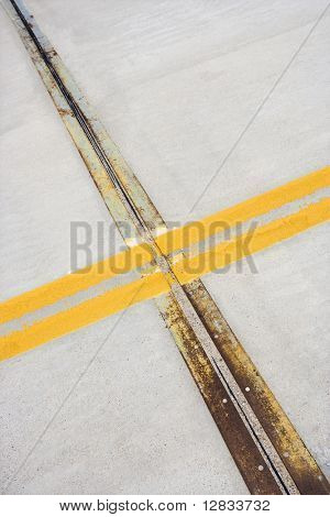 Detail of solid double yellow line in road  crossing metal strips in cement.
