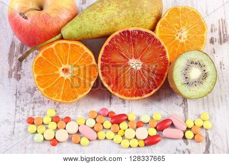 Fresh natural fruits and medical pills tablets and capsules choice between healthy nutrition and medical supplements healthy lifestyle