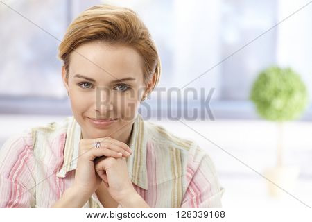 Closeup portrait of beautiful young businesswoman with short blonde hair, smiling, looking at camera, resting chin on hands.