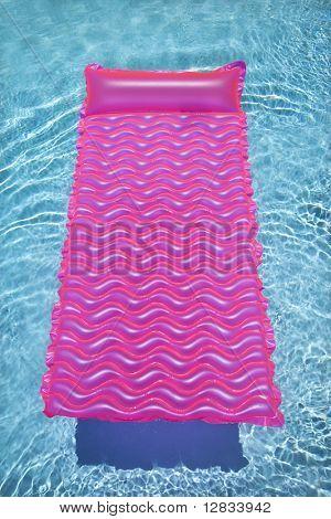 Flotador de salón rosado en piscina vacía con agua azul de ondulación.
