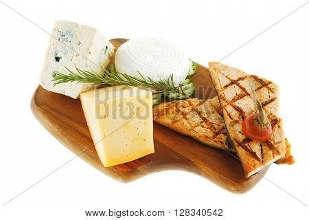 grilled sea fish salmon with french edam gorgonzola and soft feta goat cheeses on wooden plate isolated over white background