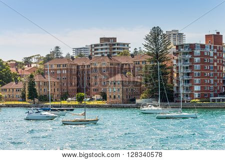 Manly Australia - November 9 2014: Sailboats moored in the Manly district bay on Summer day near Sydney Australia. Manly is a beach-side suburb of northern Sydney in the state of New South Wales Australia.