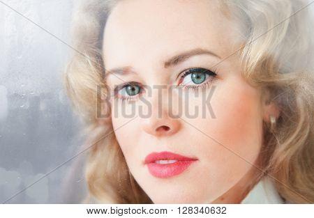 Close-up portrait of a sad beautiful woman near the window on a rainy day