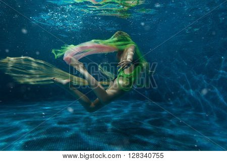 Girl swimming underwater while playing a multi-colored cloth.