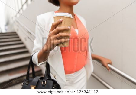 business, drinks, lifestyle and people concept - close up of young african american businesswoman with coffee cup walking downstairs to city subway