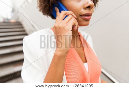 business, communication, technology and people concept - close up of african woman calling on smartphone walking downstairs to city subway