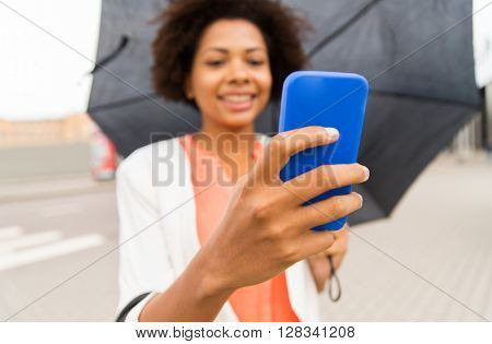 business, bad weather and people and concept - close up of happy african american businesswoman with umbrella texting on smartphone at city street