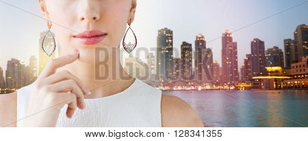 glamour, beauty, jewelry and luxury concept - close up of beautiful woman face with pearl earrings over singapore city skyscrapers background