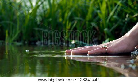 Hand over the water. Hand female, finger ring. Water is green, summer. Feng Shui