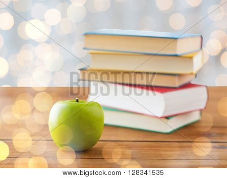 education, school, literature, reading and knowledge concept - close up of books and green apple on wooden table over holidays lights background