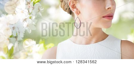 glamour, beauty, jewelry and luxury concept - close up of beautiful woman face with pearl earring over natural spring cherry blossom