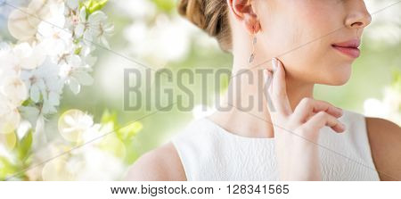 glamour, beauty, jewelry and luxury concept - close up of beautiful woman face with gold and diamond earring over natural spring cherry blossom