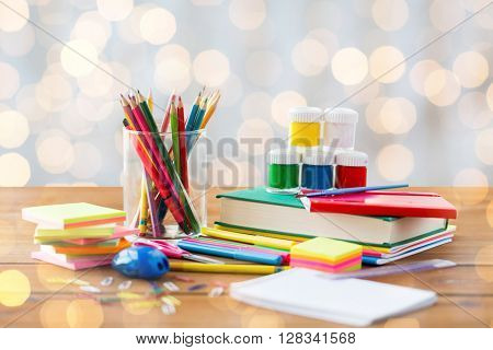 education, school supplies, art, creativity and object concept - close up of stationery on wooden table over holidays lights background