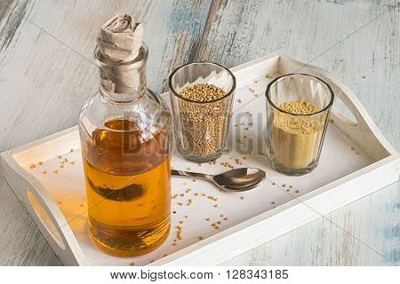 Mustard oil, mustard powder and mustard seeds in a glass crockery on a white wooden tray.