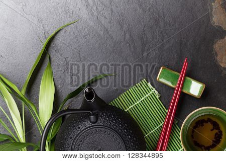 Asian tea and teapot over stone table. Top view with copy space