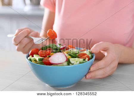 Female hand and bowl of vegetable salad on wooden table closeup