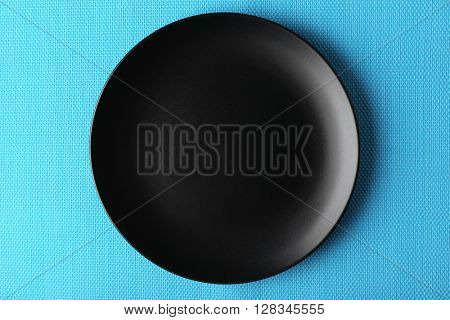 Empty plate on blue textured mat background
