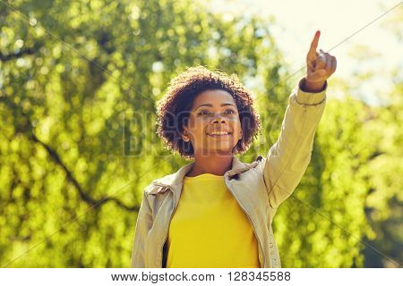 people, race, ethnicity and gesture concept - happy african american young woman pointing finger in summer park