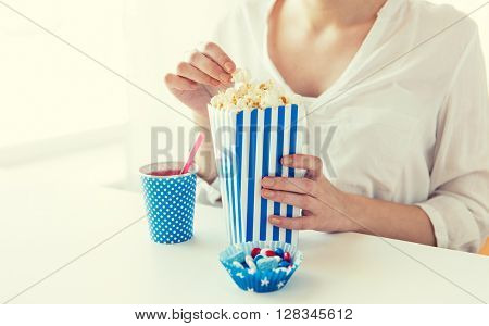 american independence day, celebration, patriotism and holidays concept - close up of woman eating popcorn with drink and candies at 4th july party